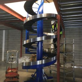 Spiral conveyor built within mezzanine floor